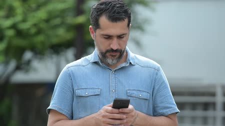 brim : Handsome Persian bearded man using phone in the streets outdoors