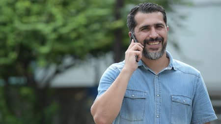 brim : Handsome Persian bearded man talking on phone in the streets outdoors
