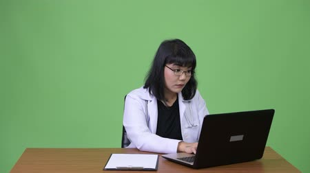 malajské : Beautiful Asian woman doctor multi-tasking at work
