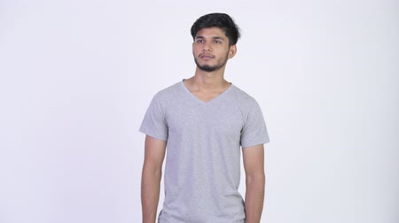 ponderar : Young handsome bearded Indian man thinking Stock Footage