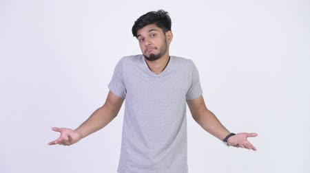 confuso : Young handsome bearded Indian man shrugging shoulders Vídeos