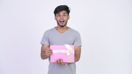 шок : Young happy bearded Indian man opening gift box and looking surprised