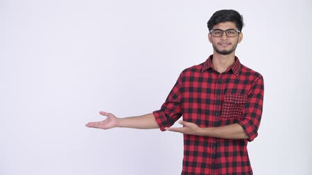 клетчатый : Young happy bearded Indian hipster man showing something Стоковые видеозаписи