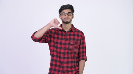 refusing : Young angry bearded Indian hipster man giving thumbs down Stock Footage