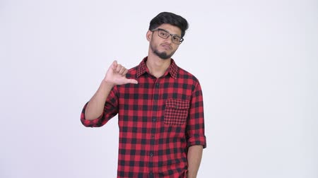 errado : Young sad bearded Indian hipster man giving thumbs down Stock Footage