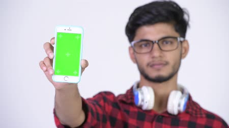 white shirt : Young happy bearded Indian hipster man showing phone