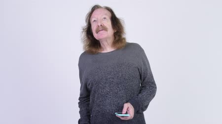 slecht nieuws : Stressed senior man with mustache using phone and getting bad news
