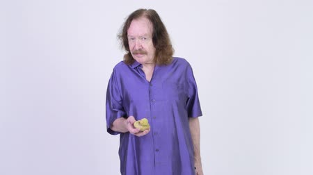poo : Happy senior man with purple silky shirt showing artificial poo Stock Footage
