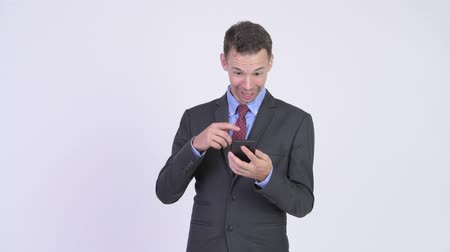 restolho : Studio shot of happy businessman using phone and getting good news
