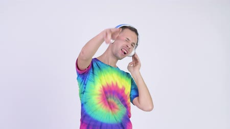 laços : Studio shot of man with tie-dye shirt wearing headphones as DJ