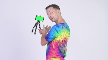 tripod shot : Studio shot of man wearing tie-dye shirt and vlogging with phone
