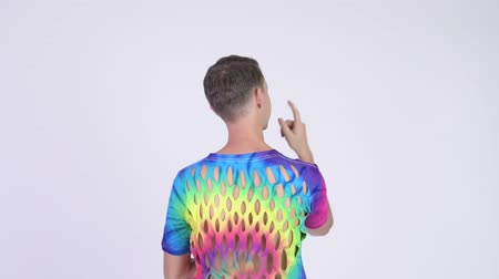 hippi : Rear view of man wearing tie-dye shirt with holes and pointing finger