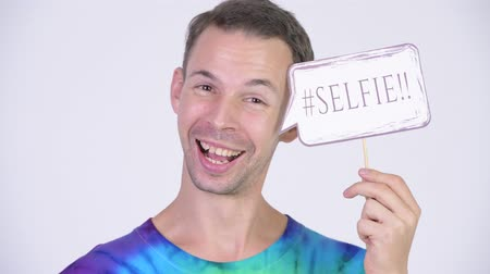 hippi : Studio shot of happy man with tie-dye shirt holding selfie paper sign Stock mozgókép