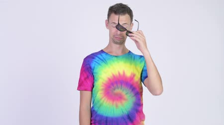 wasted : Studio shot of man with tie-dye shirt waking up after heavy partying