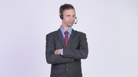 телемаркетинг : Studio shot of happy businessman as call center representative smiling with arms crossed