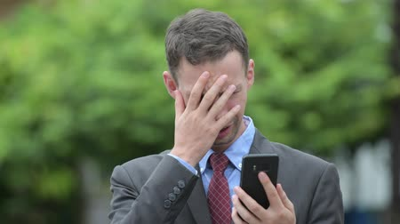 kötü : Stressed businessman using phone and getting bad news outdoors
