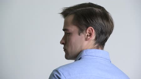 over the shoulder view : Rear view of young handsome businessman looking back Stock Footage