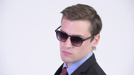 over the shoulder view : Rear view of young handsome businessman wearing sunglasses and looking back