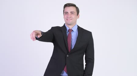 looking distance : Young happy handsome businessman pointing finger Stock Footage
