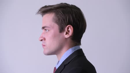 ponderando : Head shot profile view of young handsome businessman looking up