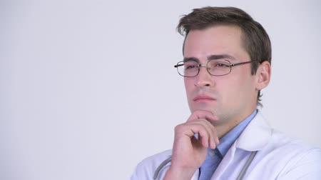 задумчивый : Young happy handsome man doctor smiling while thinking