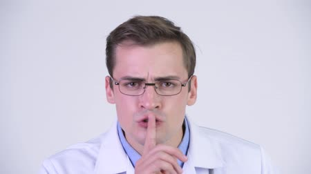 изолированные на белом : Young serious man doctor with finger on lips Стоковые видеозаписи