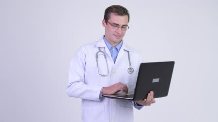 ponderar : Young happy handsome man doctor thinking while using laptop Stock Footage