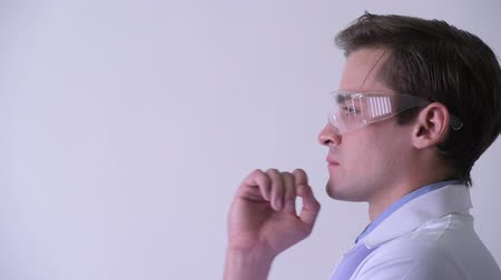 ponderar : Profile view of young handsome man doctor thinking while wearing protective glasses Stock Footage