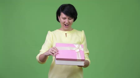 середине взрослых : Beautiful businesswoman looking surprised while opening gift box Стоковые видеозаписи