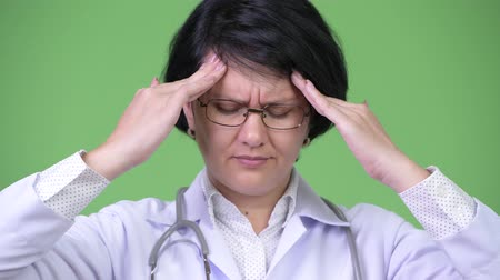médico : Stressed woman doctor with short hair having headache