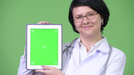 hajú : Beautiful woman doctor with short hair showing digital tablet