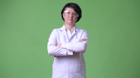 crossed : Happy beautiful woman doctor wearing protective glasses with arms crossed