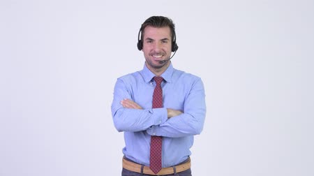 телемаркетинг : Young happy Hispanic businessman as call center representative with arms crossed Стоковые видеозаписи