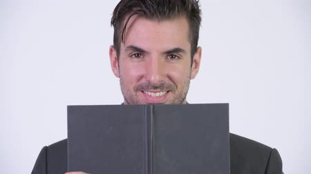hidden face : Young happy Hispanic businessman covering face with book