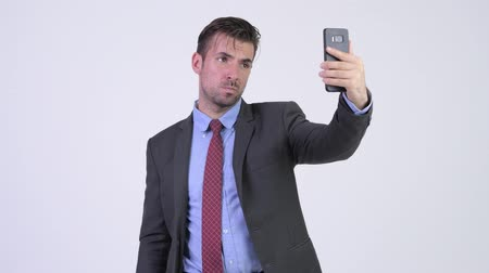 изолированные на белом : Young happy Hispanic businessman taking selfie Стоковые видеозаписи