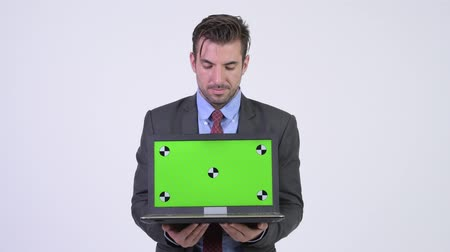 átnyújtás : Young handsome Hispanic businessman showing and looking at laptop