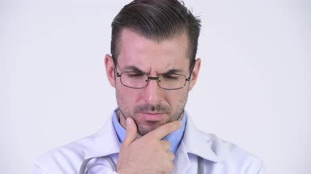 ponderar : Young serious Hispanic man doctor thinking Stock Footage