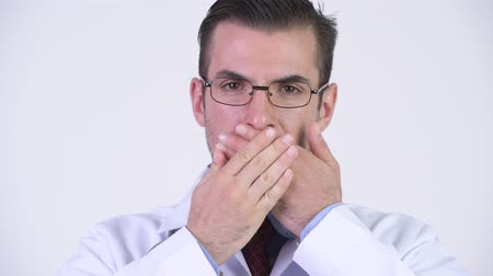 moudrý : Young Hispanic man doctor covering mouth as three wise monkeys concept Dostupné videozáznamy