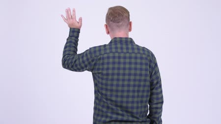 verificador : Rear view of blonde hipster man waving hand