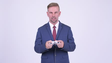 sörte : Stressed blonde businessman playing games and losing Stock mozgókép