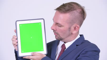 baard : Gelukkige blondezakenman die digitale tablet toont Stockvideo