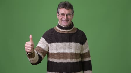 kciuk w górę : Mature handsome man wearing turtleneck sweater against green background Wideo