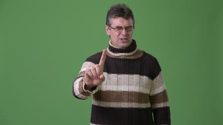 raised : Mature handsome man wearing turtleneck sweater against green background Stock Footage