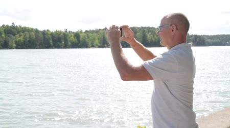 fince : Happy Senior Man Recording Video With Phone By The Lake