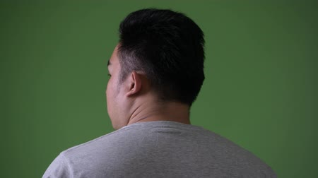 over the shoulder view : Young handsome overweight Asian man against green background