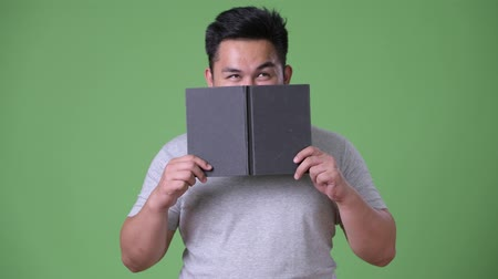 diary : Young handsome overweight Asian man against green background