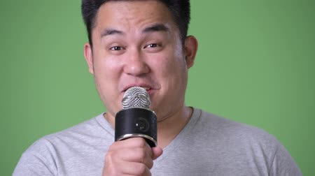노래방 : Young handsome overweight Asian man against green background
