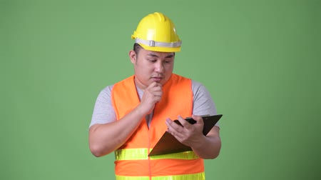 panoya : Young handsome overweight Asian man construction worker against green background