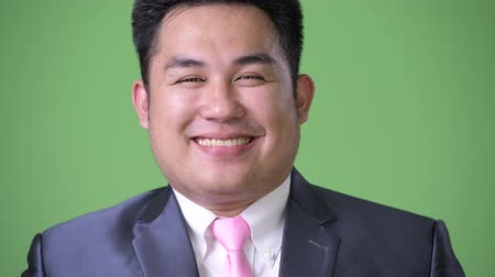 a smile : Young handsome overweight Asian businessman against green background