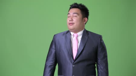 aborrecido : Young handsome overweight Asian businessman against green background